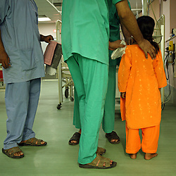 Doctors comfort a young girl before taking her into surgery at the Children's Hospital at the Pakistan Institute of Medical Sciences in Islamabad, Pakistan, Sept. 18, 2007.