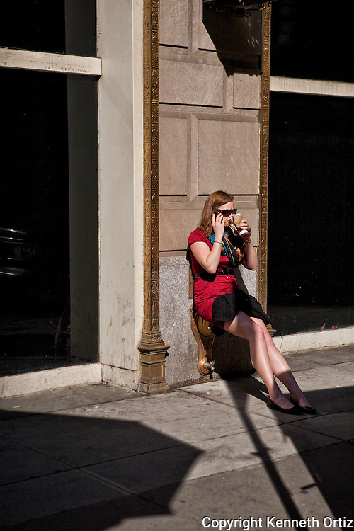 A woman in a red dress sitting down on a standpipe on 5th Avenue in Manhattan soaking up the sun while drinking coffee and talking on her cell phone. Talk about multitasking!
