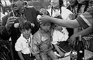 A CHILD GES A FORLOCK OF HAIR CUT OFF ON ITS THIRD BIRTHDAY, ROMAIAN ORTHODOX EASTER CELEBRATIONS. SINTESTI, ROMANIA, EASTER 1995..©JEREMY SUTTON-HIBBERT 2000..TEL./FAX. +44-141-649-2912..TEL. +44-7831-138817.