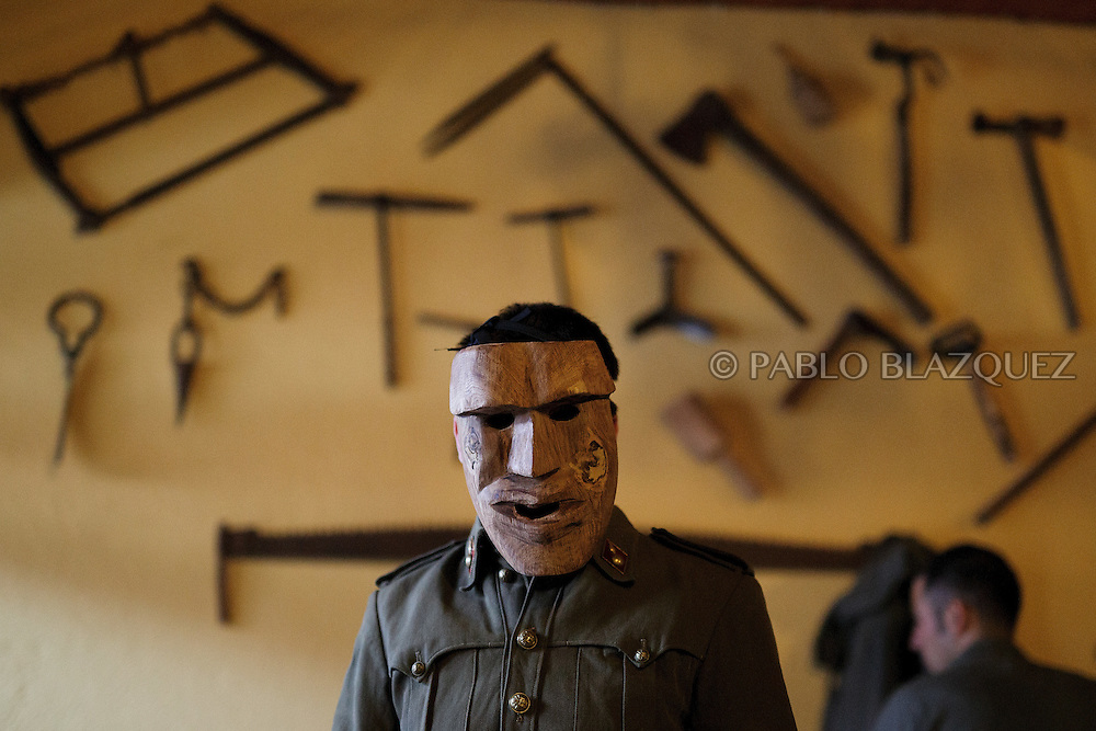 A Machurrero from Pedro Bernardo looks on as he wears a mask before walking the streets during carnival on February 6, 2016 in Pedro Bernardo, in Avila province, Spain. The origins of this pagan festival are unknown. The Machurreros wear wood masks, a military dress, black handkerchief, cowbells, and hold wicker stick. The festival disappeared after Dictator Franco forbid carnival festivals in 1937, but it was recently recovered. Before disappearing, male villagers after the military service, used to dress as Machurreros as they run along the streets scaring children and adults with their wicker stick to bring fertility to the land and expel the evil spirits. (© Pablo Blazquez)