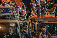 Village men wait with their Ganesha statues on the back of trucks, waiting for their chance to immerse them in the sea.  Pondicherry, India.