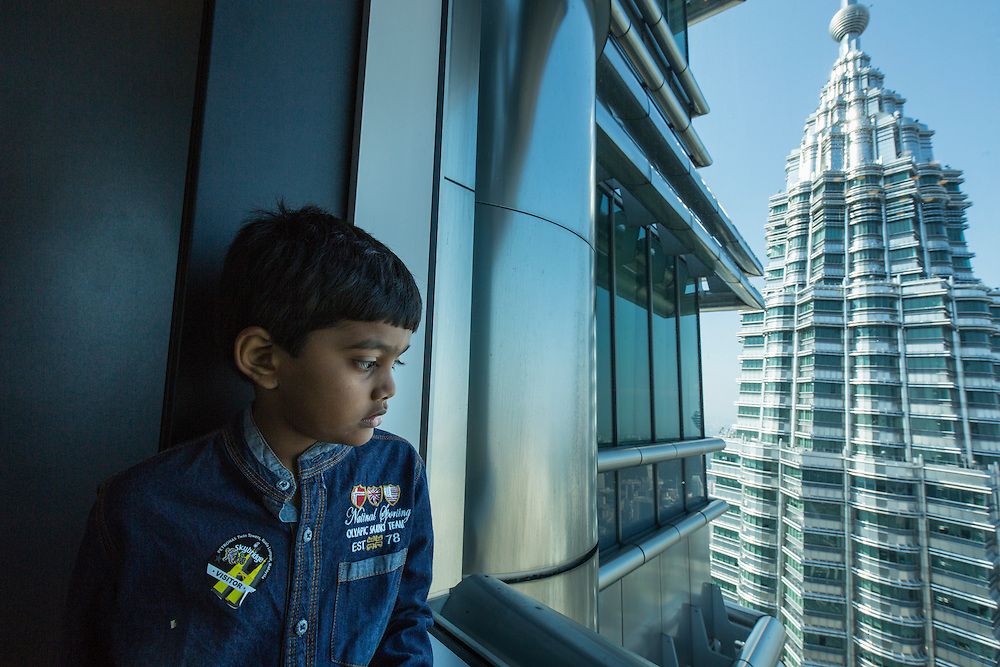 Asia, Malaysia, Kuala Lumpur, Young boy peers through window on 86th Floor Observation Deck of top of Petronas Towers