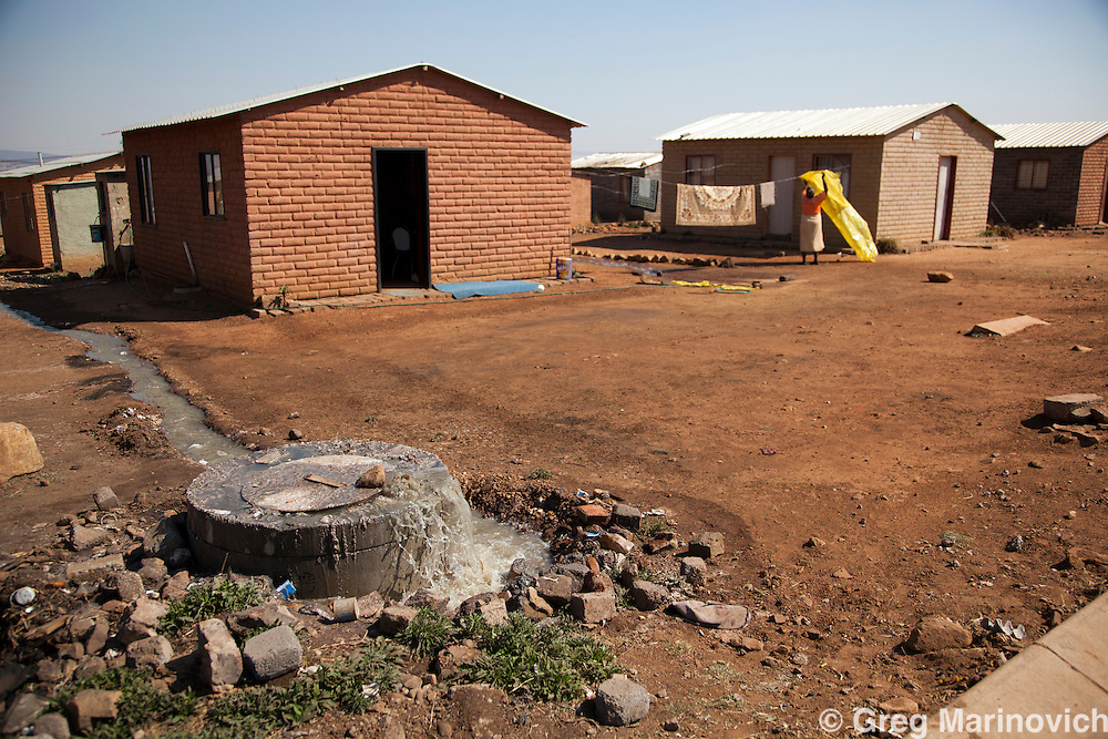 Eden Park Thokoza, East rand, Erkhululeni, South Africa. Sewerage pours out of a manhole among state funded RDP houses. Residents stated that this had been the situation for several weeks. 2010_08_18.  Greg Marinovich  / Storytaxi.com
