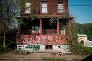 A young girl runs past an old J&amp;L company home that is slated for demolition on May 8, 2015 in West Aliquippa, Pennsylvania, USA.<br /> <br /> As foreign-born workers flocked to western Pennsylvania at the turn of the 20th century to fill jobs at the Jones &amp; Laughlin Steel mill, the company built homes for the workers. Many of these homes are still standing today.