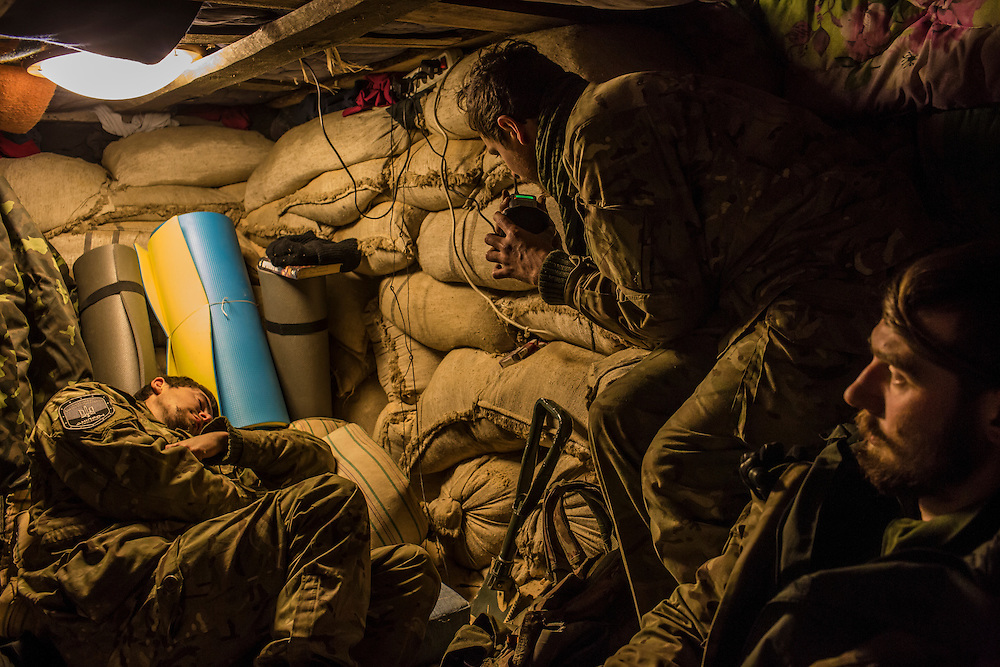 """Yaroslav Didanko, left, and Grigoriy Matyash, right, relax inside a bunker where they sleep as """"Patrick,"""" who chose not to give his name because he is from a nearby town and fears for the safety of his family, center, tests a communication radio inside a bunker where they sleep at their post underneath a bridge on November 17, 2014 in Pervomaiske, Ukraine. All are members of the 5th platoon of the Dnipro-1 brigade, a pro-Ukraine militia."""