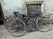"""Three old bicycles lean against a wall in Kathmandu, Nepal. Kathmandu, the largest city in Nepal (700,000 people), is sometimes called """"Kantipur"""". The city stands at an elevation of 6235 feet / 2230 meters."""
