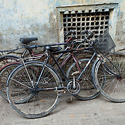 "Three old bicycles lean against a wall in Kathmandu, Nepal. Kathmandu, the largest city in Nepal (700,000 people), is sometimes called ""Kantipur"". The city stands at an elevation of 6235 feet / 2230 meters."