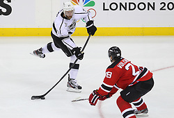 May 30; Newark, NJ, USA; Los Angeles Kings center Jeff Carter (77) shoots the puck while being defended by New Jersey Devils defenseman Anton Volchenkov (28) during the second period of 2012 Stanley Cup Finals Game 1 at the Prudential Center.  The Kings defeated the Devils 2-1.