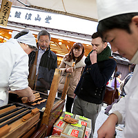 Hugh Montgomery (hand at mouth, black jacket) journalist for The Independent, and Tetsuro Hama (moustache)- owner of SO Restaurant London, try street food on sale in Kyoto, Japan, on Friday 13th January 2012.