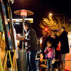 "021312       Brian Leddy.Patrick ""Cloudface"" Burnham paints on Coal Street while an audience watches during the February 11th ArtsCrawl."