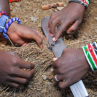 Many masais develop affections on their eyes. Tribeman making fire using straws, a knife and friction. Masai Mara tribe around the Masai Mara National Park. Kenya. East Africa.