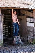 hot shirtless man standing on a rustic wheelbarrow in a barn