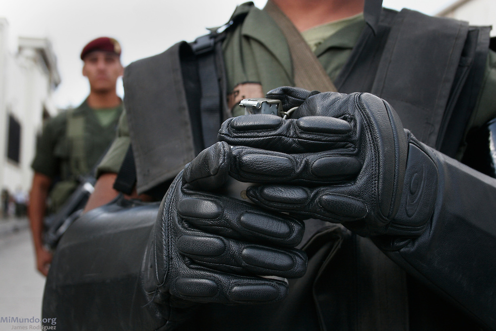 A special forces Kaibil officer stands behind another soldier holding a tear gas canister as anti-riot police block the path of the March for Remembrance southbound on 6th Avenue in Zone 1 as the Military Day festivities are being held simultaneously a block away in Guatemala City's central park. Organized by H.I.J.O.S. (Sons and Daughters for Identity and Justice Against Forgetfulness and Silence), the March for Remembrance is a counter march to the annual Military Day parade, seen by many as inadequate in modern Guatemala considering the atrocities carried out by the institution against the local population during the 36-year internal armed conflict. Guatemala City, Guatemala. June 30, 2007.