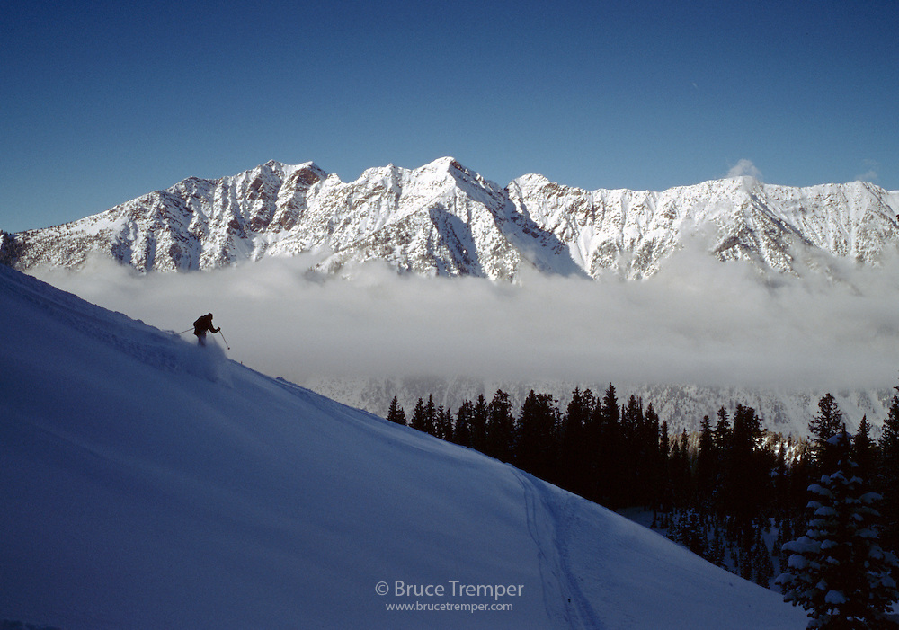 A backcountry skier descends to the road at the end of the day.  Little Cottonwood Canyon, Utah.