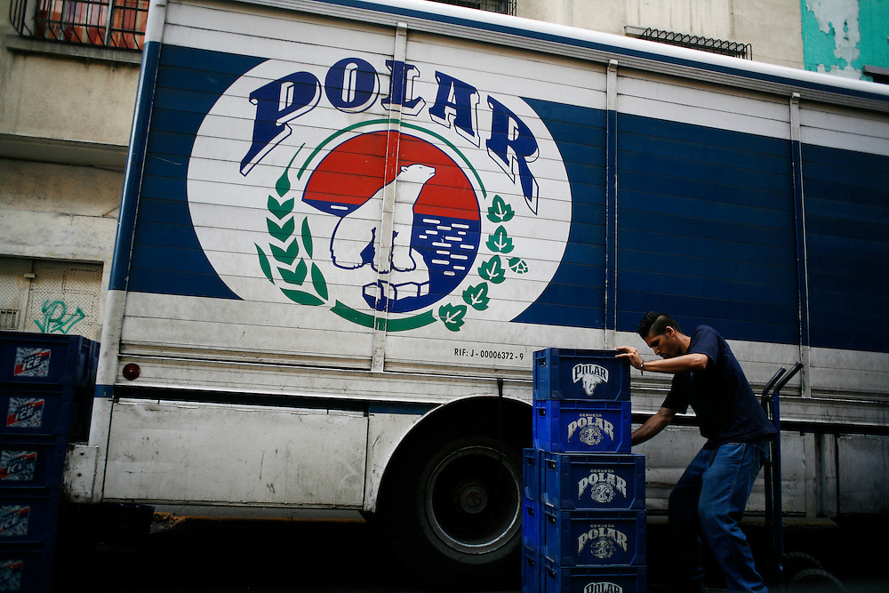 A man unloads Venezuelan Polar beer from his truck. Alcohol consumption is high in Caracas, especially on the weekends when people can be seen drinking rum or beer like Polar outside of liquor stores around the city.