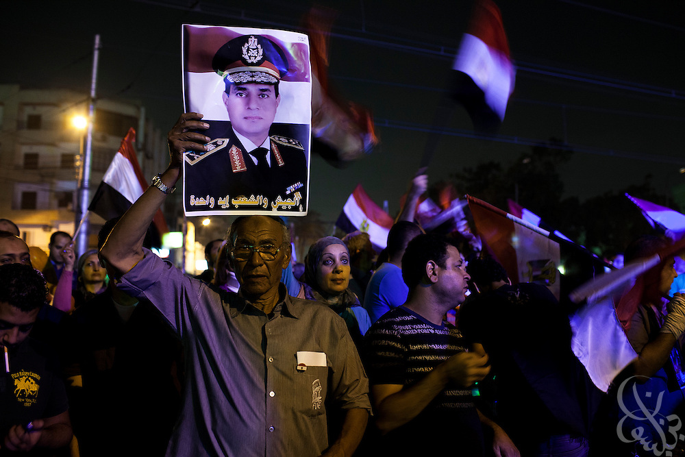 Egyptian supporters of the military's removal of ex-President Mohamed Morsi celebrate waving photos of Egyptian military head General Abdel-Fattah el-Sissi outside the Ittihadiya Presidential palace Friday, July 19, 2013 in the Heliopolis district of Cairo, Egypt. Friday was a day for both supporters and opponents to gather in various locations across Egypt to express their opinions of the recent military decision to remove Mohamed Mosi from power in early July.