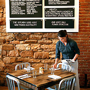 SHOT 5/16/11 3:33:53 PM - The Kitchen is a community bistro located in historic downtown Boulder, Colorado. The menu evolves seasonally and reflects the simple and straightforward preparation of comfortable classics with a focus on locally-sourced and sustainable ingredients. A server resets a table during lunch service at the restaurant. (Photo by Marc Piscotty / © 2011)