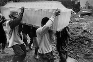 Cemetery workers carry a coffin containing the body of a victim, possibly unidentified, from the worst eruption of Mt. Merapi  in over 100 years, at a mass burial funeral ceremony at a public mass grave in a rural area near Sleman, Java, Indonesia.  The death toll from the volcanic eruption has risen to 324 people.