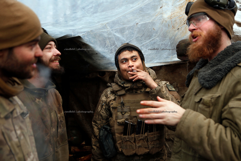 Cowboy, Alex, Charlie and Craig (le. to ri.) chatting over war issues in their trench position at donetsk frontline.<br /> <br /> Fascinated by war and convinced of a simple shaped nationalistic ideology, five vonuteer warriors from Europe and USA left behind their former lifes. Walking into battle in Ukraine, Ben, Alex, Craig, Charlie and Cowboy made it to the frontline and joint the right-wing militia Right Sector, supporting the ukrainian army which is short of staff. Receiving no payments but shelter, food and ammo the foreigners selfmade battlegroup Task Force Pluto is a loose union of individuals and no particular ukrainian phenomenon. The Boom Stick Brotherhood would move on to another conflict around the globe when Ukraine become boring to them. They want to be involved in battle. That&acute;s what they are aiming for. Living a dream of smoking guns, camaraderie and outdoor life. An extreme lifestyle devoted to an everyday look into the face of death.<br /> <br /> The Boom Stick Brotherhood is a multi-national, multi-religious and multi-ethnic group:<br /> Ben, an austrian infantryman travelling hot zones since years. Bored by his own reluctant national army at home he made plenty of experience in Kosovo, Syria, Iraq and Ukraine.<br /> Alex, Ben&acute;s brother in arms from austrian army times deserted and fled the country to get ultimately involed in frontline fights.<br /> Craig was fighting almost 6 years for the US-Army in Iraq and Afghanistan but got in conflict with the law afterwards. He escaped conviction by going abroad.<br /> Charlie was totally bored by his californian routine in Silicon Valley but failed to join the US-Army and French Foreign Legion. Eventually he found battle opportunities in Ukraine.<br /> Petty crook Cowboy got in trouble with US law only days before his Army unit was to deployed to Afghanistan. Later during a day release he made it from prison to France but French Foreign Legion rejected him. He gave Ukraine a go.