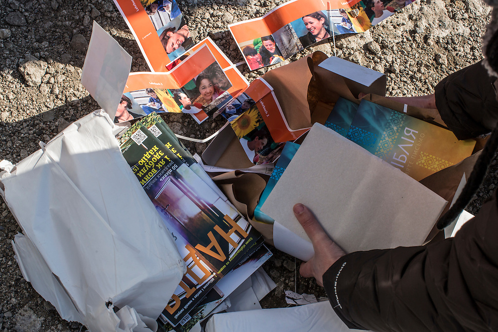 MARIINKA, UKRAINE - FEBRUARY 20, 2016:  Volunteers from the Christian Help Center of the Church of the Transfiguration collect bibles and other Christian literature distributed along with bread for those in need of humanitarian assistance in Mariinka, Ukraine. The Donetsk suburb has been the scene of some of the heaviest fighting recently between Ukrainian forces and pro-Russian rebels. CREDIT: Brendan Hoffman for The New York Times