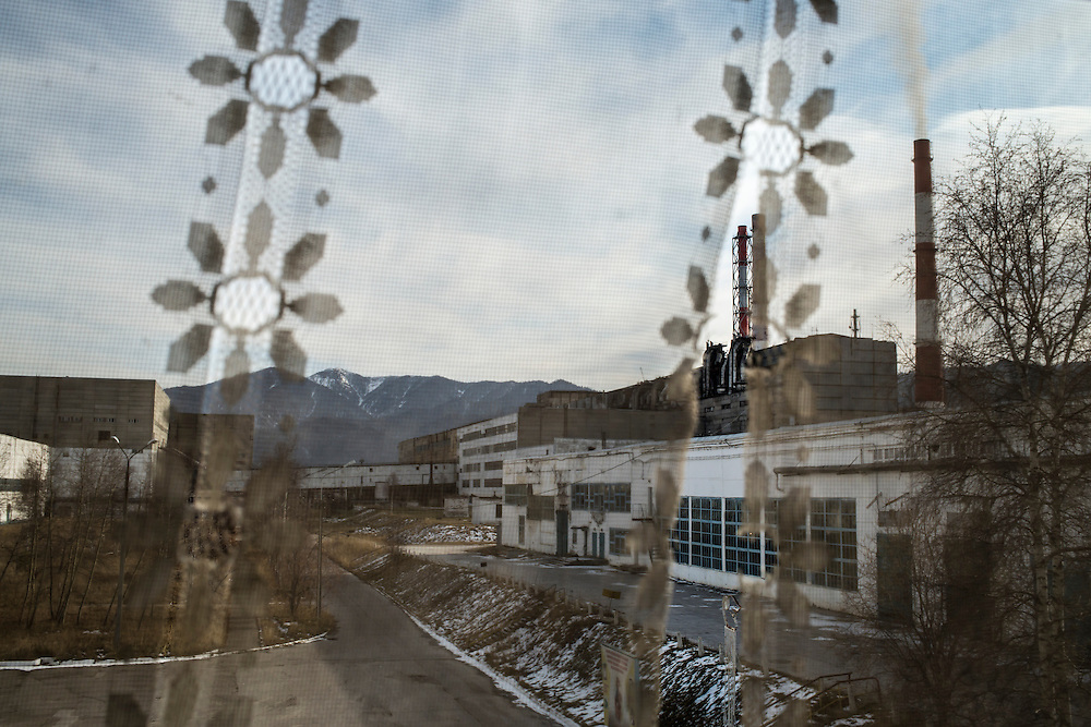 The Baikalsk Pulp and Paper Mill is visible through a lace curtain on Wednesday, October 23, 2013 in Baikalsk, Russia.
