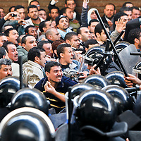 Demonstrators clash with riot police following Friday prayers in Islamic Cairo, Egypt. January 2011.