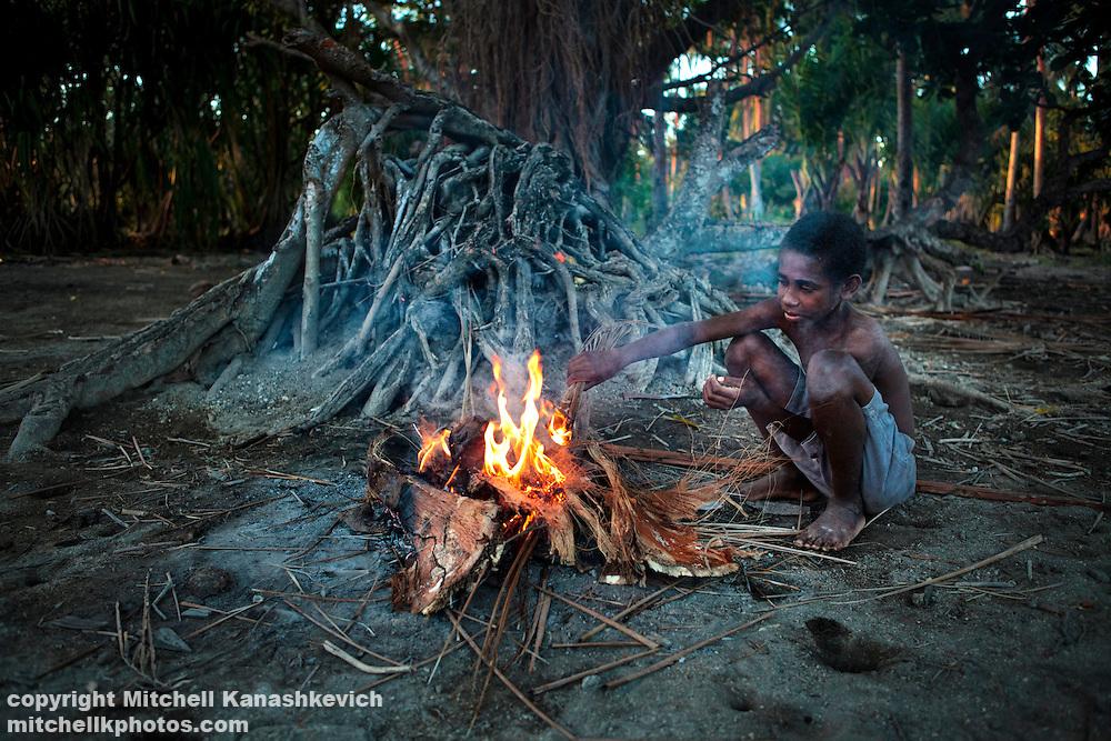 Ni Vanuatu boy  warming himself by a fire. Uleveo, Maskelyne Island, Malampa Province, Malekula, Vanuatu