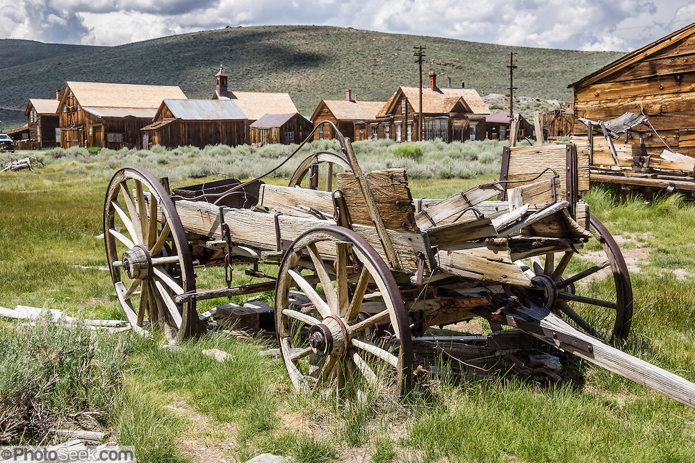 "Rustic wagon. Bodie is California's official state gold rush ghost town. Bodie State Historic Park lies in the Bodie Hills east of the Sierra Nevada mountain range in Mono County, near Bridgeport, California, USA. After W. S. Bodey's original gold discovery in 1859, profitable gold ore discoveries in 1876 and 1878 transformed ""Bodie"" from an isolated mining camp to a Wild West boomtown. By 1879, Bodie had a population of 5000-7000 people with 2000 buildings. At its peak, 65 saloons lined Main Street, which was a mile long. Bodie declined rapidly 1912-1917 and the last mine closed in 1942. Bodie became a National Historic Landmark in 1961 and Bodie State Historic Park in 1962."