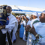 Ethiopian Jewish immigrants dance and celebrate while holding Torah Scrolls during an inauguration ceremony for a new Ethiopian Spiritual Center in Jerusalem, on June 23, 2013. The new center was funded by The International Fellowship of Christians and Jews. Photo by Oren Nahshon