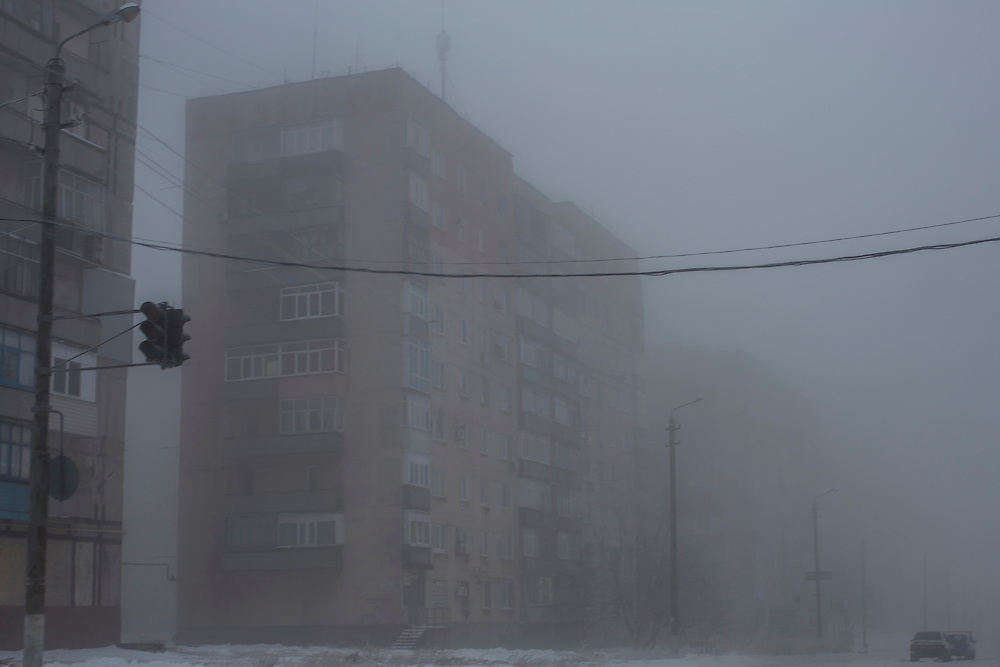 SNIZHNE, UKRAINE - DECEMBER 8, 2014: Apartment buildings seen through the fog along the road between Donetsk and Luhansk in Snizhne, Ukraine. CREDIT: Brendan Hoffman for The New York Times