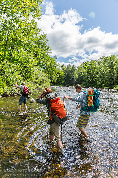 Hikers ford the Pleasant River while hiking on The Appalachian Trail in Maine's 100 Mile Wilderness.