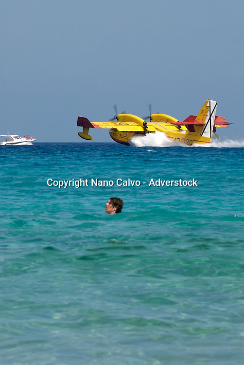 A hydroplane picking up water from a crowded Cala Nova Beach, in Santa Eulalia, while working to extinguish a fire in the area of Cala Xarraca, Ibiza
