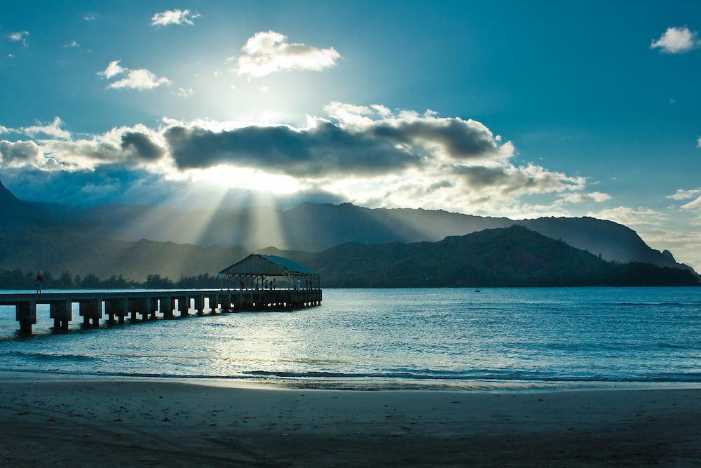 An inspiring moment as rays of  sunlight shine through the clouds on the wharf at Hanalei Bay, Kauai, Hawaii