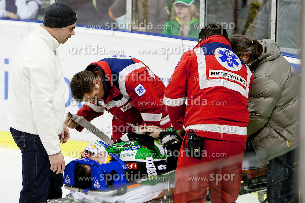 Injured Igor Cvetek (HDD Tilia Olimpija, #4) after check Dario Kostovic (KHL Medvescak Zagreb, #88) to head by during ice-hockey match between HDD Tilia Olimpija and KHL Medvescak Zagreb in 47th Round of EBEL league, on January 27, 2012 at Hala Tivoli, Ljubljana, Slovenia. (Photo By Matic Klansek Velej / Sportida)