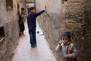 Children playing in a narrow alley inside Fez Medina.