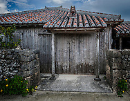 """Traditional house on the island of Taketomi Island.  Okinawa, Japan  Taketomi is a raised coral atoll 4 kilometres (2.5 mi) south of the island of Ishigaki.  In the past, only noble officials could have built a house with a red tile roof, and later, when rules were relaxed, the a red roof house was a symbol of wealth.  A stone """"shisa"""" (lion-dog) guards over the house from the roof and was generally placed about the alter where families would worship their ancesters.  The front pillars are held up by whole pieces of coral and the walls are made by hand with coral."""