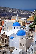 Hillside buildings with traditional church blue domes in Oia, Santorini, Greek Islands, Greece