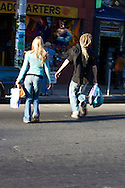 A couple j-walks acrosos Haight Street bags in hand as they shops in the Haight Ashbury district of San Francisco