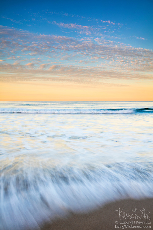A long exposure captures the motion of Pacific Ocean waves crashing onto Venice Beach in Venice, California, at sunrise.