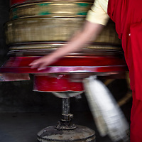 Buddhist monk in Ladakh spends a large prayer wheel.