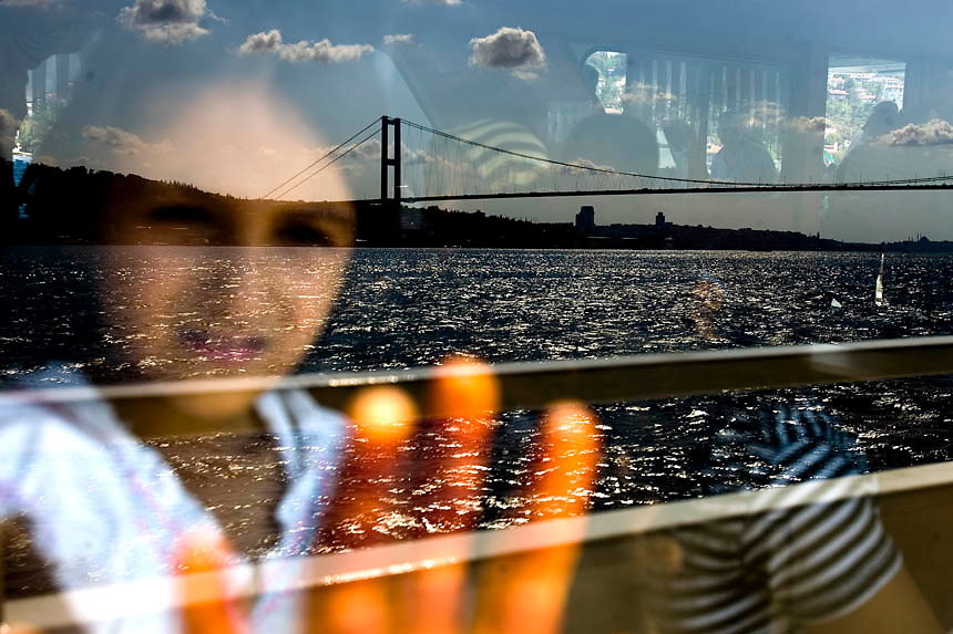The Bosphorus Bridge is reflected in the window of a ferry, touring the Bosphorus Strict