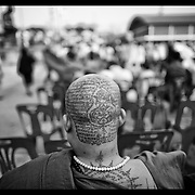 A Buddhist monk looks on during festivities at the Wat Bangpra Tattoo Festival in  Nakhon Chaisi.