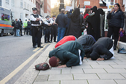 """Mayfair, London, November 28th 2014. A protest against Egypt's leader Al-Sisi descended into moinor scuffles as right wing """"patriots"""" from anti-Islamic group Britain First arrived to protest against the presence of Islamist preacher Anjem Choudary, who was recently arrestred as part of an ant-terror operation. Playing patriotic British Music, Britain First accused Muslims of worshiping a """"devil"""" and a """"paedophile prophet"""". Police had to intervene before hotheads on both sides became violent. PICTURED: Anjem Choudary, centre, prays as behind him demonstrations and counter-demonstrations continue."""