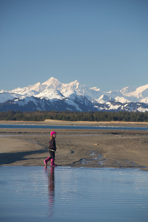 A young girl explores a tide pool along the beach in Gustavus, with Glacier Bay in the background. MR