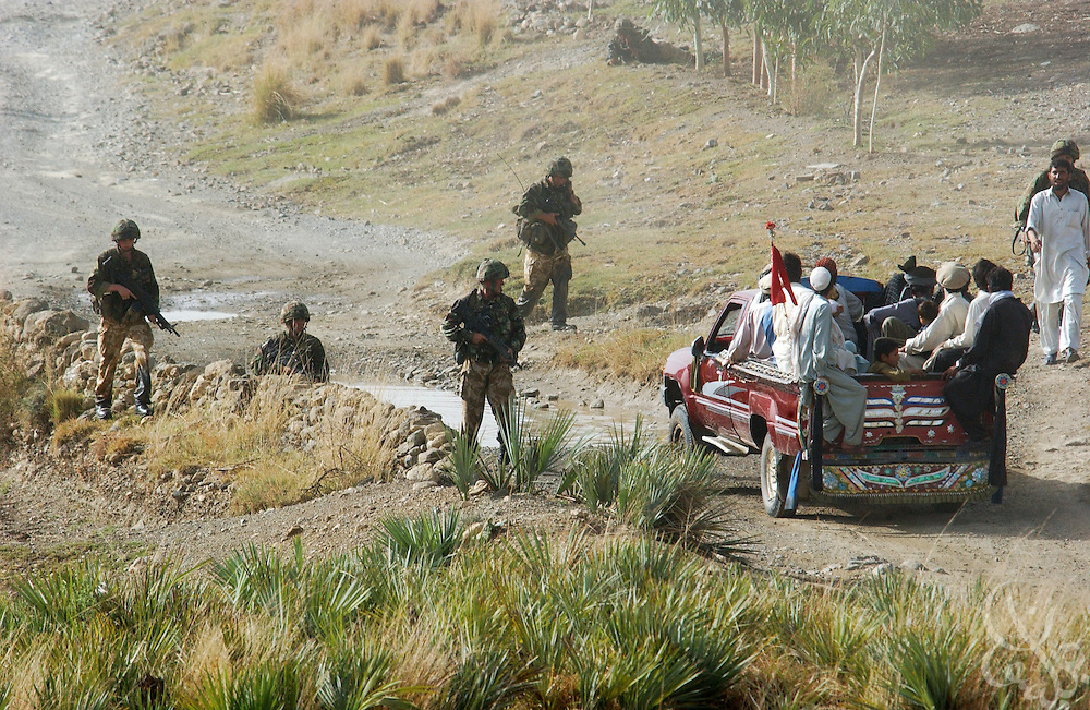 "British Royal Marine 45 Commandos search cross border traffic during an ""eagle vehicle check point"" (VCP) mission for Operation Buzzard July 8, 2002 in southeastern Afghanistan. During VCPs, small groups of marines are dropped quickly by helicopters to search random vehicles on dirt roads and trails near the Pakistan-Afghanistan border to deny al Qaeda and Taliban fighters freedom of movement across the region."