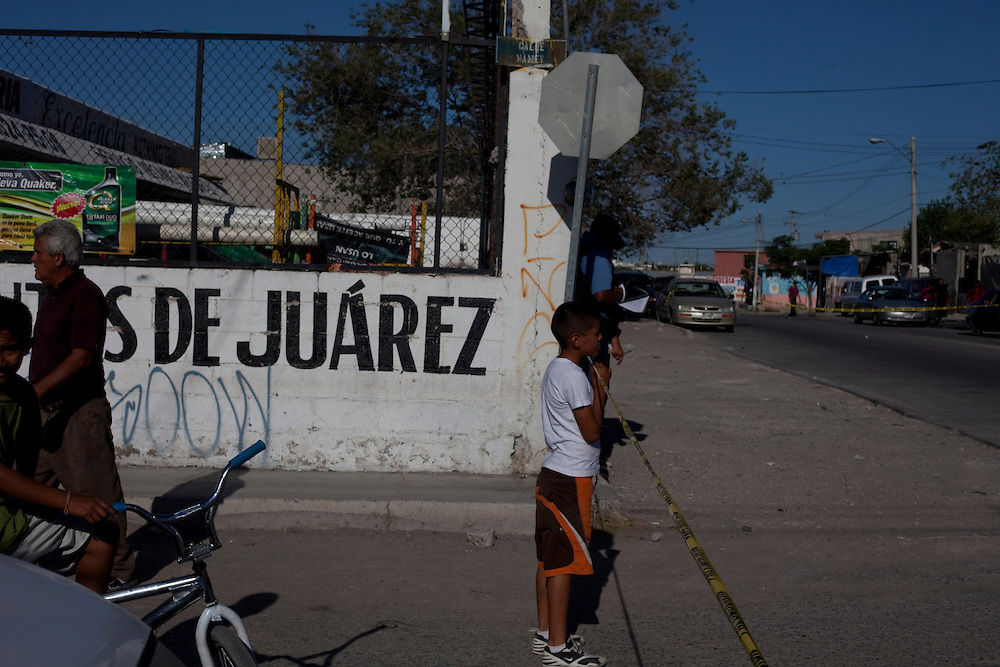 Children come to see what has happened at the scene of a murder in Ciudad Juarez, Chihuahua on May 13, 2010.