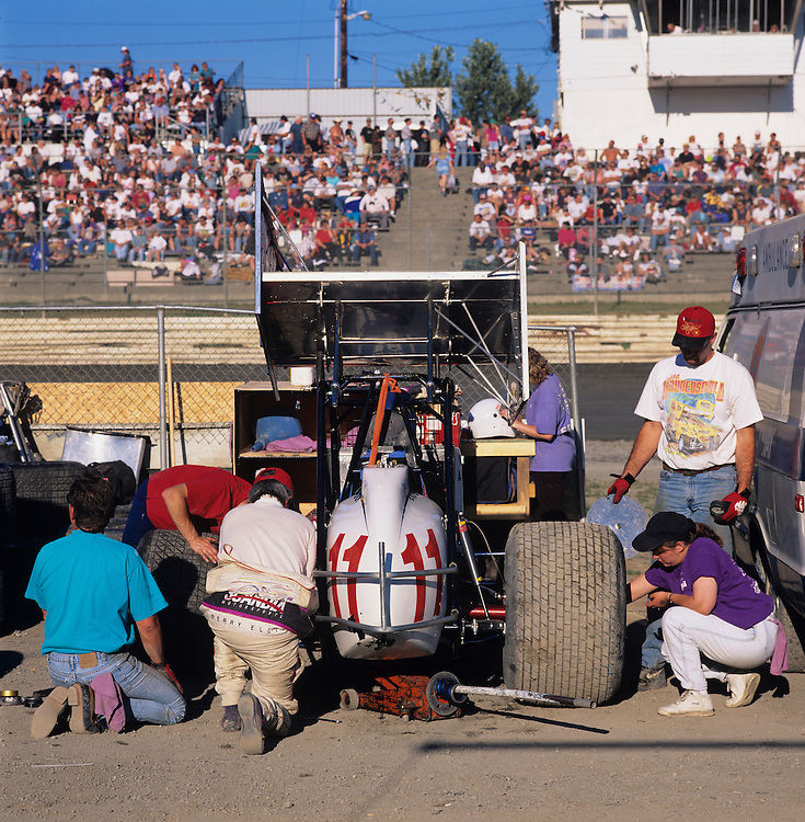 USA, Washington, Sedro Woolley, Pit crew prepares sprint car for dirt track races at Skagit Speedway on summer evening