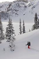 A skiier skies down toward Twin Outlets Lake in deep powder snow.  Beartooth Mountains, Montana.