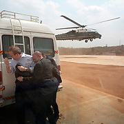 Counselor to the President Dan Bartlett is shielded by Secret Service agents as a sandstorm created by Marine One envelopes them Friday, March 3, 2006, in Hyderabad, India...Photo by Khue Bui