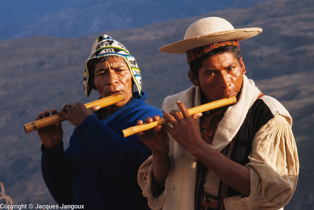 Quechua Indians playing flute at village festival in Ayata, Andes, Bolivia.
